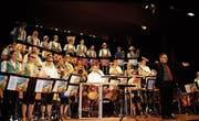 Die MG Niederhelfenschwil mit ihrem Dirigenten Marcel Eggler in ihrem Sommertenue. (Bild: Vroni Krucker)