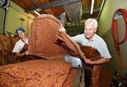 Silvia und Karl Aepli kippen den Trester – die ausgepresste Apfelmasse – auf einen Holzwagen. Er wird als Tierfutter verwendet. (Bild: Manuel Nagel)