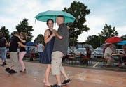 Tanzen macht auch mit Regenschirm Spass. Ein kurzer Regenschauer tat der Stimmung keinen Abbruch. (Bild: Christoph Heer)
