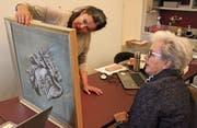 Die Kunsthistorikerin Rebekka Ray untersucht ein Gemälde, das eine Besucherin mitgebracht hat. (Bilder: Christof Lampart)