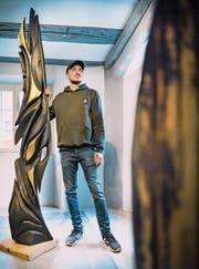 Marco Sembinelli neben einer Holzskulptur von Urs Antoine Stöcklis, die er bemalt hat. (Bild: Andrea Stalder)