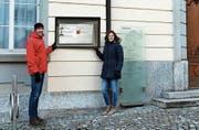 Gemeindeparlamentarier Samuel Curau und J&A-Aktuarin Anina Curau präsentieren einen möglichen Infoscreen-Standort am Rathaus. (Bild: PD)