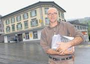 Kunsthallen-Präsident Roland Rüegg verteilt schon mal Plakate zur Kunstaktion. Im Hintergrund das Hotel-Restaurant Post in Ebnat-Kappel, wo das Kultur-Hotel im Juni eine Woche Gastrecht hat. (Bild: Hansruedi Kugler)