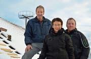 Hans Thomann, Lisbeth Kuhn und Felix Raschle freuen sich über die Installation des Storchennests auf dem Scheunendach. (Bild: Mario Testa)