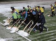 Aufwärmen der anderen Art: Ersatzspieler und Junioren des FC Wil schaufeln den Kunstrasen für das Testspiel frei. (Bild: Simon Dudle)