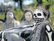 Vorchristliche Traditionen und Glaube an Magie: Eine als Skelett bemalte Frau raucht bei einem Ritual in Papua-Neuguinea. (Bild: getty/Eric Lafforgue)