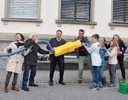 Mitglieder des Vereins Solardorf Rehetobel (links) schliessen die Schule symbolisch an die Solaranlage an. (Bild: gia)