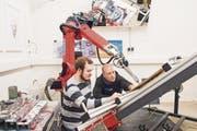 Die beiden Informatiker Marvin Gülzow und Thomas Lindemeier (rechts) begutachten das neuste Werk des Malroboters e-David. (Bild: Thi My Lien Nguyen)