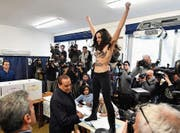 Ex-Premier Silvio Berlusconi wurde gestern im Wahllokal in Mailand von einer Femen-Aktivistin empfangen. (Bild: Daniel Dal Zennario/EPA)