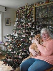 Elvira Bissegger sitzt mit einer ihrer drei Katzen vor dem Christbaum. (Bild: Yvonne Aldrovandi-Schläpfer)