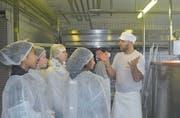 Aus hygienischen Gründen tragen die Schülerinnen Schutzkleidung, während sie den Weg der Milch zu Käse verfolgen. (Bild: Ramona Riedener)