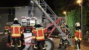 Angehörige der Feuerwehr machen die Anhängeleiter für die Personenrettung bereit. (Bild: PD)