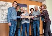 Sie teilen sich Brot vor den Plakaten der Fastenzeit: Alex Hutter, Rose-Marie Macher, Peter Baumann, Vreni Dietemann, Verena Fankhauser, Christof Kaiser, René Oettli und Edith Heiniger. (Bild: Samuel Koch)