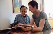Margrit Raimann, Leiterin Zentrum Wiitsicht, stöbert mit einem Bewohner der Pflegegruppe in Erinnerungen. (Bild: Ursula Wegstein)