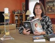 Schriftstellerin Sabine Ibing schmökert im Wohnzimmer durch ihre selbstgeschriebenen Bücher. (Bild: Amy Douglas)