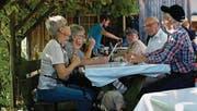 Unter der schattenspendenden Pergola geniessen die Gäste am Winzerfest die gute Atmosphäre.