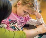 Die Klassen-Assistentin stützt Darias Arm, während sie schreibt. (Bild: Reto Martin (Reto Martin))