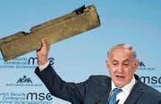Der israelische Ministerpräsident Benjamin Netanjahu hält während seiner Rede ein Teil einer abgeschossenen iranischen Drohne in die Luft. (Bild: EPA (München, 18. Februar 2018))