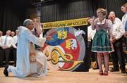 Die Ehrendamen Seraina Räss und Melanie Burkhalter halten die Vereinsfahne, während Pfarrer Marcel Ruepp sie segnet. (Bild: Monika Wick)