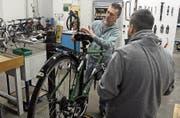 Franz Schwarz erklärt in der neuen Velowerkstatt einem stellenlosen Mann eine Reparaturarbeit. (Bild: PD)
