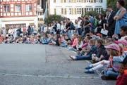 Gespannt sitzen die Kinder vor dem Schulhaus Kirchplatz in Wil. (Bild: Yves Weibel)