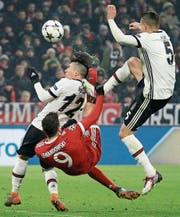 Münchens Doppeltorschütze Robert Lewandowski (rot) behauptet den Ball gegen Pepe (rechts) und Gary Medel. (Bild: Roland Wittek/EPA)