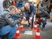 Der Schrein mit der Fliege Erika wird in den Boden der HSG eingelassen: Stifter Hans-Dietrich Reckhaus (im Anzug) und die Künstlerzwillinge Patrik und Frank Riklin (mit Mützen) sind an vorderster Front dabei. (Bild: Hanspeter Schiess)