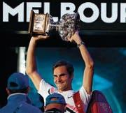 Roger Federer stemmt nach seinem Sieg gegen Marin Chilic seinen Siegerpokal in die Höhe. (Bild: Vincent Thian/AP Photo)