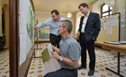 Bauamtschef Martin Belz (kniend) erklärt zwei Immobilienverwaltern im Foyer des Rathauses die Änderungen am Zonenplan. (Bild: Mario Testa)