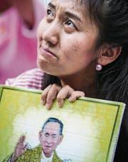 Eine Thailänderin in Trauer über den Tod ihres Königs. (Bild: Diego Azubel/EPA)