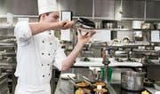 Ein Koch bei der Speisezubereitung in einer Hotelküche. (Bild: Christian Beutler/Keystone (Zürich, 30. März 2017))