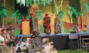 Mowgli das Dschungelkind, angenommen von den Wölfen, behütet von Bär Baloo und Panther Bagheera (links der Schülerchor).