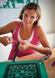 Kunsthandwerk mit Miniatur-Charakter: Jolanda Brändle arbeitet an einem Scherenschnitt, rechts das fertige Olma-Plakat. (Bilder: Ralph Ribi/olma)