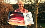 Jürg Wiesli mit den Riesen-Chilis und der Urkunde des Guinnessbuch der Rekorde. (Bild: PD)