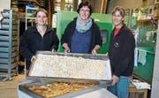 Vor dem grünen Ofen: Isabelle Baumberger, Claudia Gemperli und Gabi Graf sind die Herrinnen des Dörrbetriebs. (Bild: Maya Heizmann)