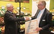 Münchwilens Gemeindepräsident Guido Grütter (l.) erhält von Martin Romer, Leiter Fachmarkt und Gastronomie Migros Ostschweiz, einen Scheck über 5000 Franken. (Bild: Christof Lampart)