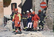 A woman on a wheelchair is carried away by rescuers in Norcia, central Italy, after an earthquake with a preliminary magnitude of 6.6 struck central Italy, Sunday, Oct. 30, 2016. A powerful earthquake rocked the same area of central and southern Italy hit by quake in August and a pair of aftershocks last week, sending already quake-damaged buildings crumbling after a week of temblors that have left thousands homeless. (Matteo Crocchioni/ANSA via AP) (Bild: Matteo Crocchioni (AP))