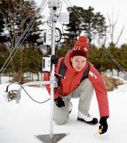 Fabian Wolfsperger misst die Schneetemperatur neben einer seiner Messstationen. (Bild: Andreas Eisenring)