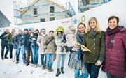 Sie wünschen sich einen Kinderhort: Eine Gruppe Eltern posiert mit den Petitionärinnen vor der Raiffeisen-Baustelle, wo ein Generationenraum entsteht. Dieser wäre ein möglicher Standort. (Bild: Andrea Stalder)