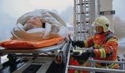 Mittels Hubretter wurde die bettlägerige Patientin auf einem Rettungsbrett geborgen. (Bild: iks)