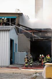 Feuerwehrleute bekämpfen den Brand in der Metallverarbeitungsfirma. (Bild: Stefan Hilzinger (20. März 2014))