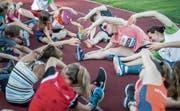 Aufwärmen gehört zum Sport: Diese Lektion erteilt Weltstar Sally Pearson (Mitte) den Kindern und Jugendlichen in Frauenfeld und geht mit gutem Beispiel voran. (Bild: Reto Martin)