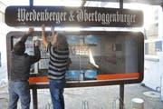 Korrektor Ernst Hobi und Reinigungskraft Werner Graf montieren den Schaukasten ab. (Bild: Ursula Wegstein)