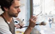 Mathias Truniger bei der Arbeit mit der Neubeschriftung der Kaffeerösterei Baumgartner in der St. Galler Altstadt. (Bild: Joa Schmid, Büro Sequenz)