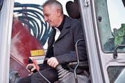 Spatenstich: Bauherr Ruedi Menet hebt die erste Schaufel mit dem Bagger aus. (Bild: IKS)