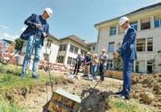 Stadtpräsident Anders Stokholm und Hiag-CEO Martin Durchschlag versenken die Kiste mit Unterlagen zum Walzmühle-Projekt in einer Grube. Damit ist der Grundstein für eine Umgestaltung des ehemaligen Industrieareals gelegt. (Bild: Donato Caspari)