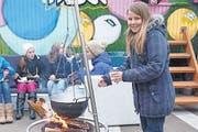 Kira von der Jugendarbeit Müllheim kocht Tee am offenen Feuer: Im Hintergrund das bunte «Rolling House». (Bild: Marlies Kunz)