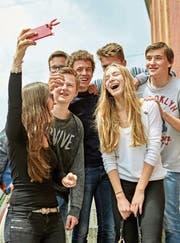 Eine Gruppe Jugendlicher macht mit einem Smartphone ein Selfie. (Bild: Christof Schuerpf/KEY)