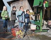 Kinder probieren den frisch gepressten Most, während das flüssige Gold aus der Presse heraus in den Kübel fliesst. (Bild: Yvonne Aldrovandi-Schläpfer)