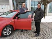Gemeinderat Bernhard Braun bei der Schlüsselübergabe mit Rolf Gehrig von Mobility Carsharing vor dem Gemeindehaus. Ab April gibt es in Eschlikon einen festen Mobility-Stammplatz mit Elektroauto und dazugehöriger Ladesäule. (Bild: PD)